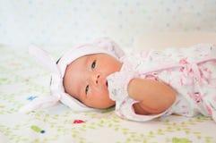 Céntrese en el bebé con la venda agradable mientras que dormita y juega con la muñeca linda en la cama La muchacha recién nacida  Foto de archivo libre de regalías