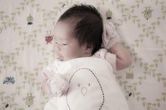 Céntrese en el bebé con la venda agradable mientras que dormita y juega con la muñeca linda en la cama La muchacha recién nacida  Imagenes de archivo