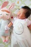 Céntrese en el bebé con la venda agradable mientras que dormita y juega con la muñeca linda en la cama La muchacha recién nacida  Foto de archivo