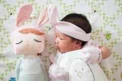 Céntrese en el bebé con la venda agradable mientras que dormita y juega con la muñeca linda en la cama La muchacha recién nacida  Imágenes de archivo libres de regalías