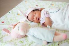 Céntrese en el bebé con la venda agradable mientras que dormita y juega con la muñeca linda en la cama La muchacha recién nacida  Imagen de archivo