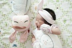 Céntrese en el bebé con la venda agradable mientras que dormita y juega con la muñeca linda en la cama La muchacha recién nacida  Fotografía de archivo