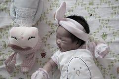 Céntrese en el bebé con la venda agradable mientras que dormita y juega con la muñeca linda en la cama La muchacha recién nacida  Fotografía de archivo libre de regalías