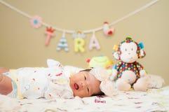 Céntrese en el bebé mientras que dormita y juega en la cama Fotos de archivo
