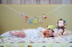 Céntrese en el bebé mientras que dormita y juega en la cama Fotografía de archivo