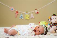 Céntrese en el bebé mientras que dormita y juega en la cama Imagen de archivo