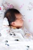 Céntrese en el bebé mientras que dormita y juega en la cama Fotografía de archivo libre de regalías