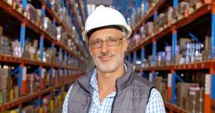 Céntrese en el trabajador del almacén que sonríe a la cámara almacen de metraje de vídeo