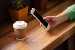 Céntrese en la mujer del inconformista que usa smartphone con la bebida fotos de archivo libres de regalías