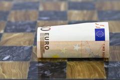 Céntrese en la nota euro lanzada en tablero del juego Foto de archivo