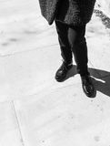 Céntrese en las piernas de la mujer que llevan abarcas del cuero del negro del estilo de Londres Imagen de archivo libre de regalías