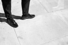 Céntrese en las piernas de la mujer que llevan abarcas del cuero del negro del estilo de Londres Fotos de archivo