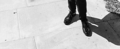 Céntrese en las piernas de la mujer que llevan abarcas del cuero del negro del estilo de Londres, Fotografía de archivo libre de regalías