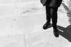 Céntrese en las piernas de la mujer que llevan abarcas del cuero del negro del estilo de Londres Foto de archivo