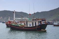 Céntrese en un barco de pesca entre muchos amarrado delante de pueblo foto de archivo