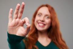 Céntrese en un gesto del éxito dado por la mujer del pelirrojo Foto de archivo libre de regalías