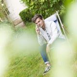 Céntrese en un hombre joven que da una llamada de teléfono al aire libre Fotografía de archivo libre de regalías