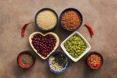 Céréale alimentaire, légumineuses, graines et poivrons de piment superbes sur un fond brun Chia, quinoa, haricots, sarrasin, lent images stock