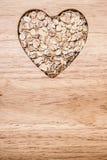 Céréale d'avoine en forme de coeur sur la surface en bois Image stock