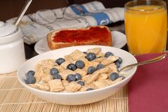 Céréale de blé avec les myrtilles, le pain grillé, le jus d'orange et le journal Photographie stock libre de droits