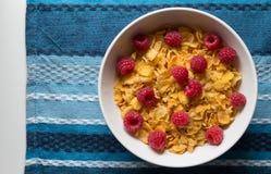 Céréale de petit déjeuner des cornflakes et des framboises sur le CCB bleu de tissu Photographie stock libre de droits