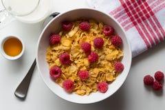 Céréale de petit déjeuner des cornflakes et les framboises, le miel et le lait o Images libres de droits