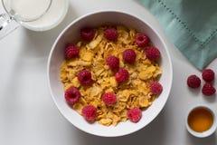 Céréale de petit déjeuner des cornflakes et les framboises, le miel et le lait o Image libre de droits