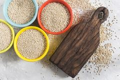 Céréale organique de quinua dans la cuvette de couleur sur le fond blanc Photos libres de droits