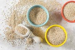 Céréale organique de quinua dans la cuvette de couleur sur le fond blanc Photographie stock
