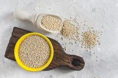 Céréale organique de quinua dans la cuvette de couleur sur le fond blanc Photo stock