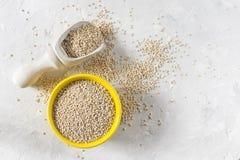 Céréale organique de quinua dans la cuvette de couleur sur le fond blanc Images libres de droits