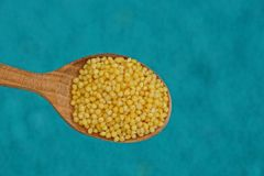 Céréale ronde jaune dans une cuillère en bois sur un fond bleu Photographie stock