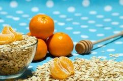 Céréale sur la table, les mandarines et la cuillère pour le miel Photos stock