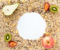 Céréales étendues sur le fond avec des fruits frais Photo libre de droits