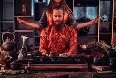 Cérémonie de thé chinoise Couples dans des vêtements traditionnels orientaux pendant une cérémonie de thé chinoise dans la chambr images libres de droits