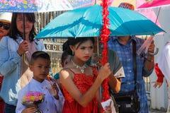 Cérémonie l'épousant sur la rue Fille dans une robe rouge sous un parapluie image libre de droits