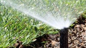Césped de riego del sistema de espray de la irrigación del jardín Foto de archivo libre de regalías