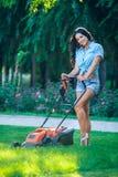 Césped de siega de la mujer en jardín trasero residencial Fotos de archivo