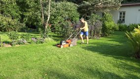 Césped de siega del hombre masculino del paisajista en la yarda de su casa de la granja 4K almacen de video