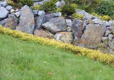 Césped hermoso con un jardín de piedras Foto de archivo