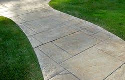 Césped y calzada pavimentada Fotografía de archivo