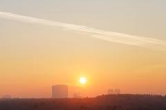Céu alaranjado do nascer do sol sobre a cidade no inverno frio Imagens de Stock Royalty Free
