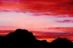 Céu alaranjado e roxo vermelho brilhante durante o por do sol sobre montanhas pretas em Yellowstone Imagem de Stock Royalty Free