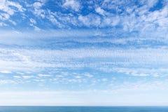 Céu azul bonito sobre o mar com translúcido, branco, nuvens de cirro foto de stock