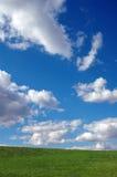 Céu azul brilhante com nuvens e grama Foto de Stock