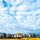 Céu azul com nuvens brancas e construções residenciais no horizonte imagens de stock royalty free