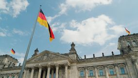 Céu azul da mola sobre a construção do Bundestag em Alemanha Bandeiras alemãs que acenam no vento vídeos de arquivo