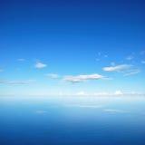 Céu azul e nuvens com reflexão na água do mar Fotografia de Stock Royalty Free