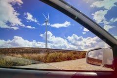 céu azul ensolarado em um campo do moinho de vento de um carro Imagens de Stock Royalty Free