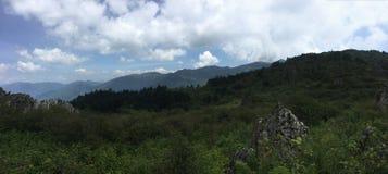 C?u azul, montanhas vazias, montanhas na dist?ncia, verde, e muitas nuvens brancas no c?u fotografia de stock royalty free